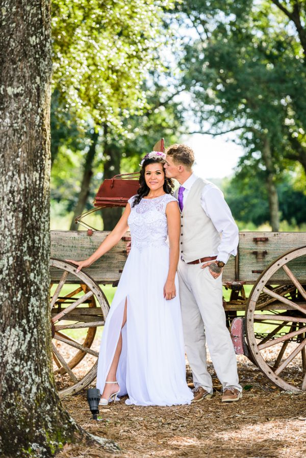 Brent kissing Michelle on the head and Michelle looking at the camera in front of the old wagon, Ates Ranch Wedding Barn, Rustic Barn Wedding, Pensacola wedding photographer, Lazzat Photography