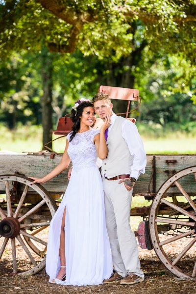 Michelle smiling at Brent and touching his face while Brent looks at camera by the old wagon, Ates Ranch Wedding Barn, Rustic Barn Wedding, Pensacola wedding photographer, Lazzat Photography