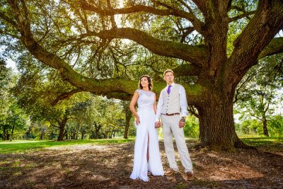 Michelle and Brent looking away from each other under the big tree, Ates Ranch Wedding Barn, Rustic Barn Wedding, Pensacola wedding photographer, Lazzat Photography