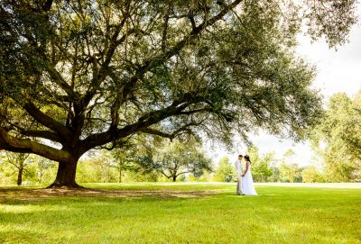 Michelle and Brent facing each other and looking down under the big tree, Ates Ranch Wedding Barn, Rustic Barn Wedding, Pensacola wedding photographer, Lazzat Photography