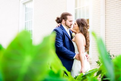 Downtown Pensacola Wedding, Cody and Kerri smiling at each other, photo through the leaves, Lazzat Photography