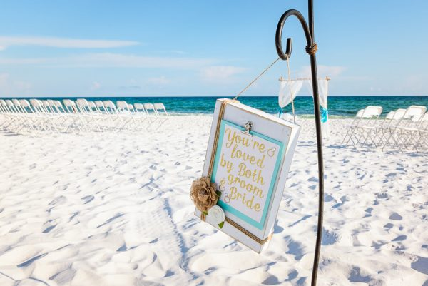 "Pensacola Beach Destination Wedding, ""you're loved by both he groom and bride"" sign at Desireé and Delaine's beach wedding, Lazzat Photography"