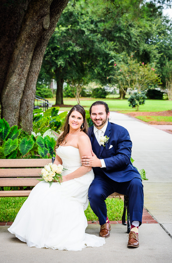 Downtown Pensacola Wedding, Cody and Kerri smiling at the camera while sitting on the bench, Lazzat Photography