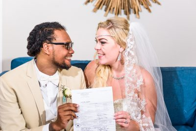 Pensacola Beach Destination Wedding, Desireé and Delaine holding their marriage certificate, Lazzat Photography