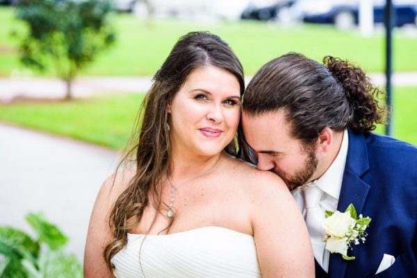 Downtown Pensacola Wedding, close up of Kerri looking at the camera and Cody kissing her shoulder, Lazzat Photography