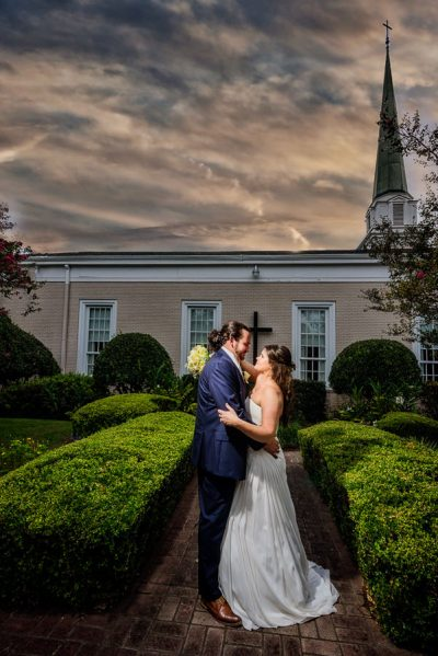Downtown Pensacola Wedding, Cody and Karri looking at each other with dramatic clouds in front of church, Lazzat Photography