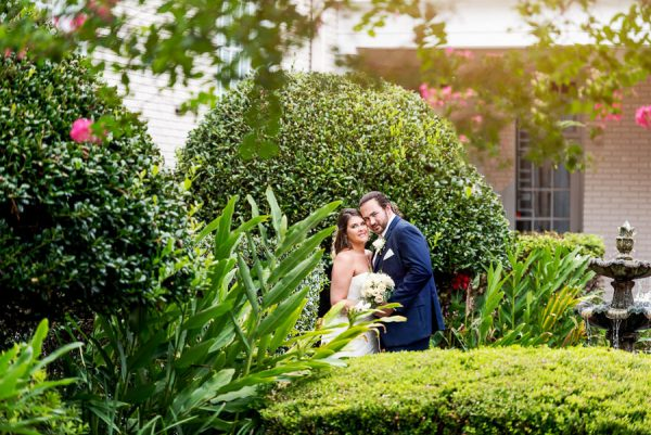 Downtown Pensacola Wedding, Cody and Karri looking at camera in garden, Lazzat Photography