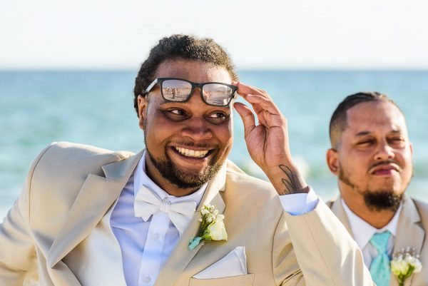 Pensacola Beach Destination Wedding, close up of Delaine raising his glasses and looking at Desireé walking down the aisle, Lazzat Photography