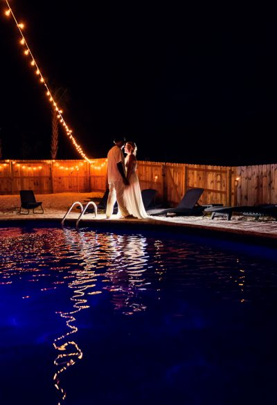 Pensacola Beach Destination Wedding, Delaine and Desireé backlit and looking at each other by the pool with reflection, Lazzat Photography
