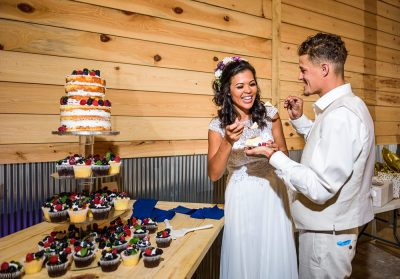 Michelle and Brent feeding each other cake at Ates Ranch Wedding Barn, Rustic Barn Wedding, Pensacola wedding photographer, Lazzat Photography