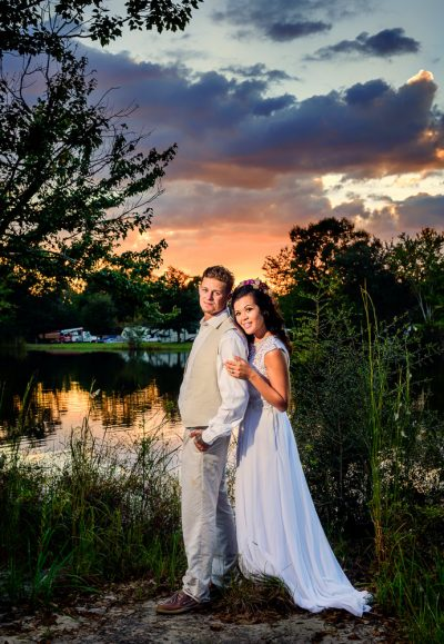 Michelle and Brent looking at the camera at sunset outside Ates Ranch Wedding Barn, Rustic Barn Wedding, Pensacola wedding photographer, Lazzat Photography
