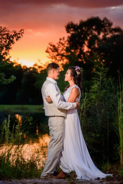 Michelle and Brent looking at each other at sunset outside Ates Ranch Wedding Barn, Rustic Barn Wedding, Pensacola wedding photographer, Lazzat Photography
