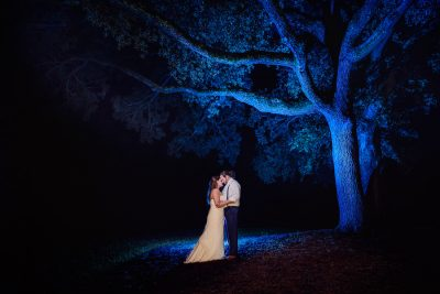 Downtown Pensacola Wedding, Kerri + Cody standing under blue tree, Lazzat Photography