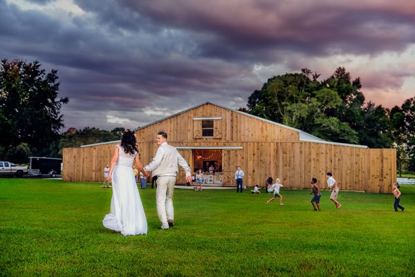 Brent and Michelle walking towards the Ates Ranch Wedding Barn with kids playing in the background, Rustic Barn Wedding, Pensacola wedding photographer, Lazzat Photography