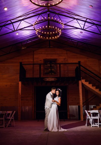 Brent kissing Michelle and Michelle looking at the camera under the chandlers in the Ates Ranch Wedding Barn, Rustic Barn Wedding, Pensacola wedding photographer, Lazzat Photography