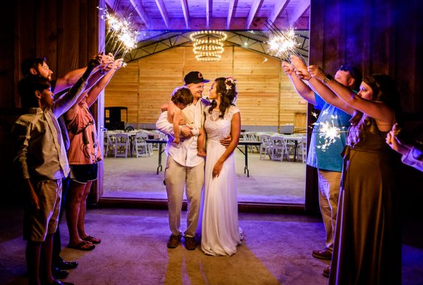 Michelle+Brent looking at each other during their sparkler exit at Ates Ranch Wedding Barn, Rustic Barn Wedding, Pensacola wedding photographer, Lazzat Photography