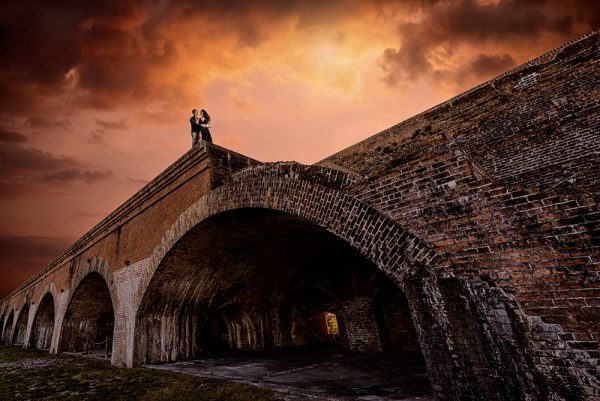 Timber+Alec at the edge of the wall with epic sunset and arches during their Ft. Pickens Sunset Engagement Session, Timber+Alec, Ft. Pickens Sunset Engagement Session, Pensacola engagement photographer, Pensacola engagement photo session, Pensacola engagement photos, Pensacola engagement photography, Lazzat Photography
