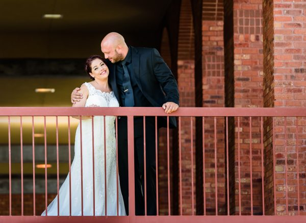 Hill looking at Ashley and Ashley smiling at the camera along the railing, Pensacola Waterfront Wedding, Ashley+Hill, Lazzat Photography