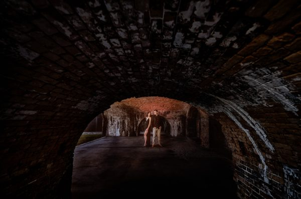 shot of Timber+Alec though the tunnel at Ft. Pickens during their Sunset Engagement Session, Timber+Alec, Ft. Pickens Sunset Engagement Session, Pensacola engagement photographer, Pensacola engagement photo session, Pensacola engagement photos, Pensacola engagement photography, Lazzat Photography
