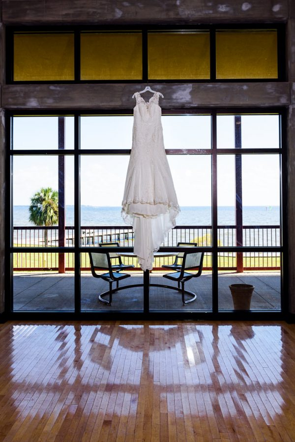 Ashley's wedding dress hanging in front of the windows overlooking the water, Pensacola Waterfront Wedding, Ashley+Hill, Lazzat Photography