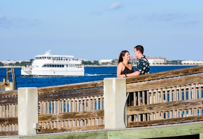 Timber+Alec smiling at each other on the pier during their Ft. Pickens Sunset Engagement Session, Timber+Alec, Ft. Pickens Sunset Engagement Session, Pensacola engagement photographer, Pensacola engagement photo session, Pensacola engagement photos, Pensacola engagement photography, Lazzat Photography