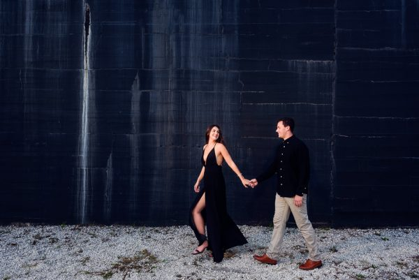 Timber leading Alec in front of the black painted wall during their Ft. Pickens Sunset Engagement Session, Timber+Alec, Ft. Pickens Sunset Engagement Session, Pensacola engagement photographer, Pensacola engagement photo session, Pensacola engagement photos, Pensacola engagement photography, Lazzat Photography