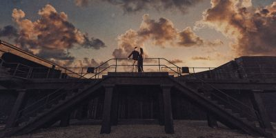 Timber+Alec looking at each other on the landing between two staircases with an epic sky during their Ft. Pickens Sunset Engagement Session, Timber+Alec, Ft. Pickens Sunset Engagement Session, Pensacola engagement photographer, Pensacola engagement photo session, Pensacola engagement photos, Pensacola engagement photography, Lazzat Photography