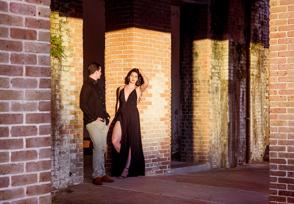 Timber+Alec leaning against opposite walls, Alec looking at Timber and Timber looking at the camera during their Ft. Pickens Sunset Engagement Session, Timber+Alec, Ft. Pickens Sunset Engagement Session, Pensacola engagement photographer, Pensacola engagement photo session, Pensacola engagement photos, Pensacola engagement photography, Lazzat Photography
