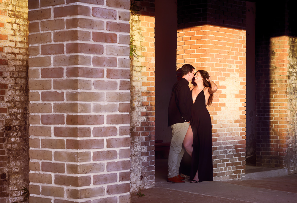 Alec leaning against Timber on the brick wall smiling at each other during their Ft. Pickens Sunset Engagement Session, Timber+Alec, Ft. Pickens Sunset Engagement Session, Pensacola engagement photographer, Pensacola engagement photo session, Pensacola engagement photos, Pensacola engagement photography, Lazzat Photography