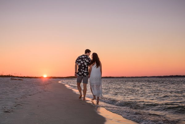 Timber+Alec walking down the beach towards the sunset smiling at each other during their Ft. Pickens Sunset Engagement Session, Timber+Alec, Ft. Pickens Sunset Engagement Session, Pensacola engagement photographer, Pensacola engagement photo session, Pensacola engagement photos, Pensacola engagement photography, Lazzat Photography