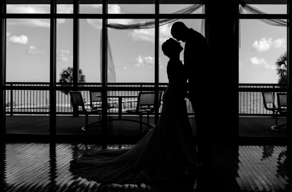 silhouette of Ashley and Hill in front of the windows at their venue, black and white, Pensacola Waterfront Wedding, Ashley+Hill, Lazzat Photography