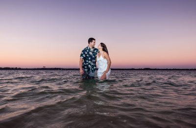 Timber+Alec standing in the water smiling at each other during their Ft. Pickens Sunset Engagement Session, Timber+Alec, Ft. Pickens Sunset Engagement Session, Pensacola engagement photographer, Pensacola engagement photo session, Pensacola engagement photos, Pensacola engagement photography, Lazzat Photography