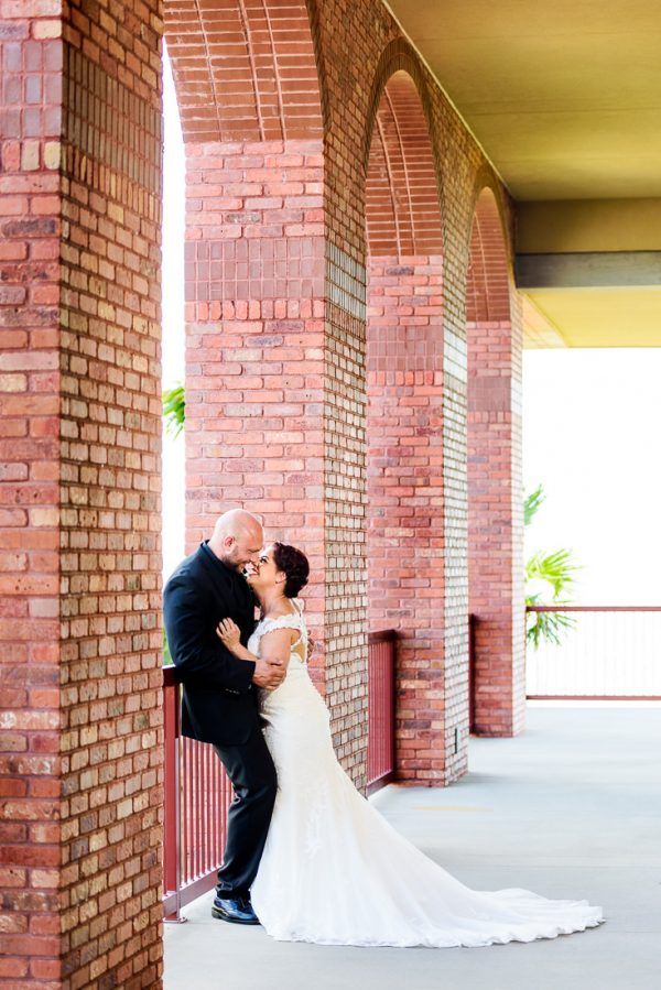 Ashley leaning on Hill almost kissing in front of the arches at their venue, Pensacola Waterfront Wedding, Ashley+Hill, Lazzat Photography