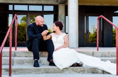 Hill and Ashley looking at each other smiling sitting on the steps in front of their venue, Pensacola Waterfront Wedding, Ashley+Hill, Lazzat Photography