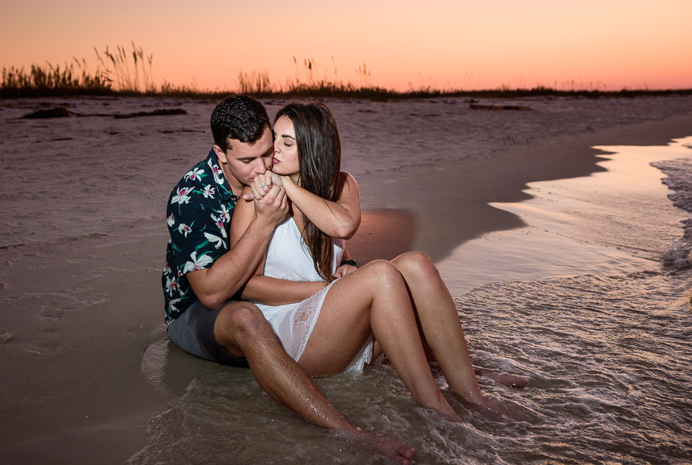 Alec kissing Timber's hand and Timber kissing his cheek while sitting on the beach during their Ft. Pickens Sunset Engagement Session, Timber+Alec, Ft. Pickens Sunset Engagement Session, Pensacola engagement photographer, Pensacola engagement photo session, Pensacola engagement photos, Pensacola engagement photography, Lazzat Photography