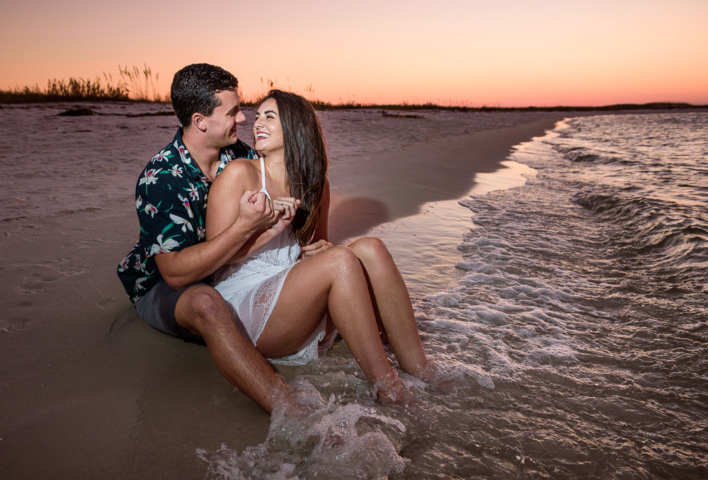 Timber+Alec doing pinky promise and smiling at each other while sitting on the beach during their Ft. Pickens Sunset Engagement Session, Timber+Alec, Ft. Pickens Sunset Engagement Session, Pensacola engagement photographer, Pensacola engagement photo session, Pensacola engagement photos, Pensacola engagement photography, Lazzat Photography