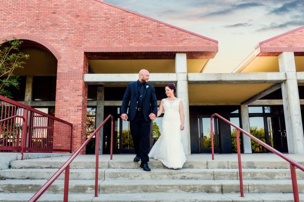 Hill and Ashley walking down the steps in front of their venue, Pensacola Waterfront Wedding, Ashley+Hill, Lazzat Photography