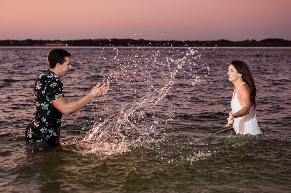 Timber+Alec splashing each other with water during their Ft. Pickens Sunset Engagement Session, Timber+Alec, Ft. Pickens Sunset Engagement Session, Pensacola engagement photographer, Pensacola engagement photo session, Pensacola engagement photos, Pensacola engagement photography, Lazzat Photography