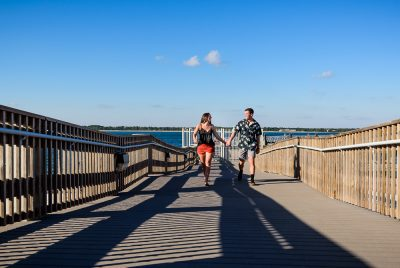 Timber+Alec walking along the pier during their Ft. Pickens Sunset Engagement Session, Timber+Alec, Ft. Pickens Sunset Engagement Session, Pensacola engagement photographer, Pensacola engagement photo session, Pensacola engagement photos, Pensacola engagement photography, Lazzat Photography