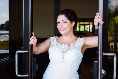 Ashley holding the doors open and smiling at the camera, Pensacola Waterfront Wedding, Ashley+Hill, Lazzat Photography
