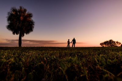 silhouette of Hill leading Ashley through the grass at sunset, Pensacola Waterfront Wedding, Ashley+Hill, Lazzat Photography