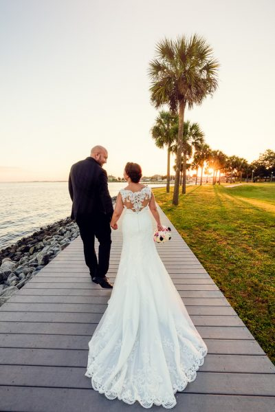 Ashley and Hill walking down the sidewalk in front of the water at sunset, photo through the grass, Pensacola Waterfront Wedding, Ashley+Hill, Lazzat Photography
