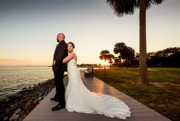 Ashley hugging Hill from the back in front of the water at sunset, photo through the grass, Pensacola Waterfront Wedding, Ashley+Hill, Lazzat Photography