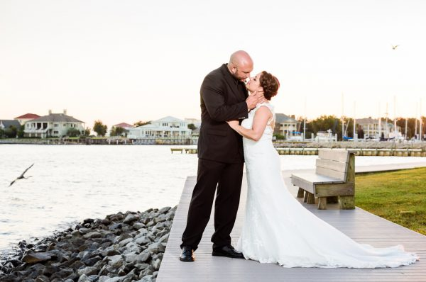 Ashley and Hill almost kissing in front of the water at sunset, photo through the grass, Pensacola Waterfront Wedding, Ashley+Hill, Lazzat Photography