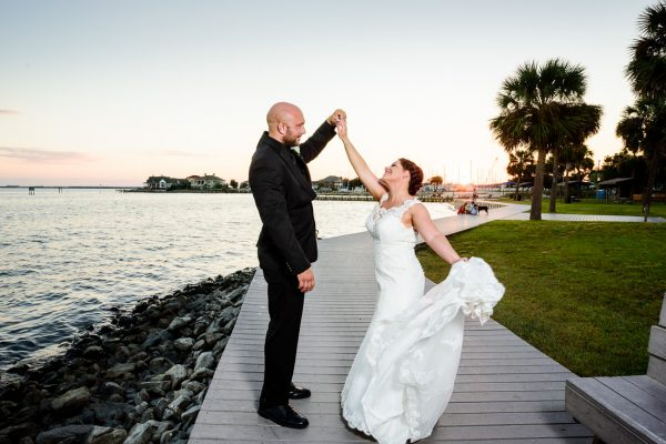 Hill spinning Ashely in front of the water at sunset, photo through the grass, Pensacola Waterfront Wedding, Ashley+Hill, Lazzat Photography