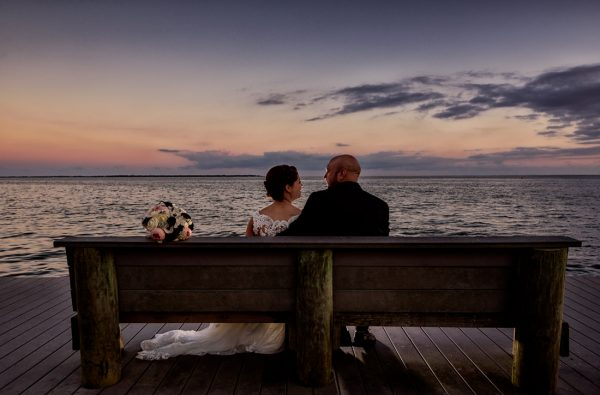 Ashley and Hill sitting on a bench looking at each other in front of the water at sunset, photo through the grass, Pensacola Waterfront Wedding, Ashley+Hill, Lazzat Photography
