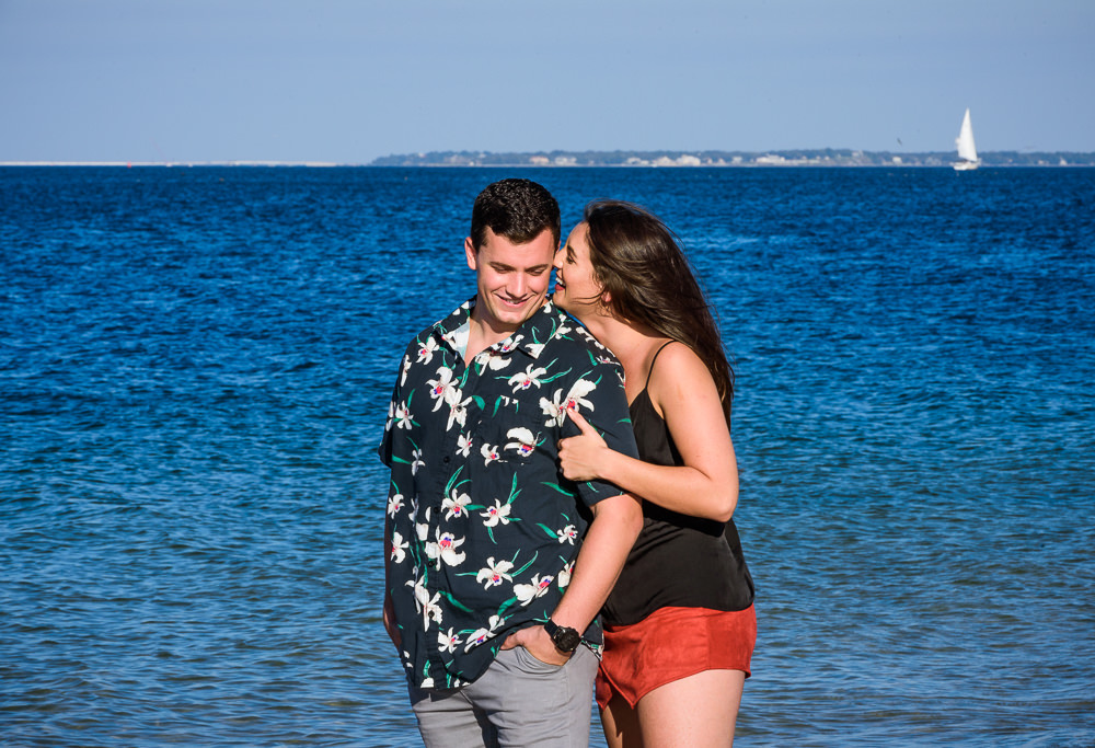 Timber whispering to Alec on the beach with sailboat in the background during their Ft. Pickens Sunset Engagement Session, Timber+Alec, Ft. Pickens Sunset Engagement Session, Pensacola engagement photographer, Pensacola engagement photo session, Pensacola engagement photos, Pensacola engagement photography, Lazzat Photography