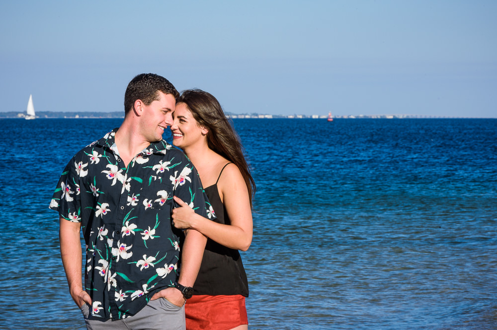 Timber+Alec head to head smiling at each other on the beach with sailboat in the background during their Ft. Pickens Sunset Engagement Session, Timber+Alec, Ft. Pickens Sunset Engagement Session, Pensacola engagement photographer, Pensacola engagement photo session, Pensacola engagement photos, Pensacola engagement photography, Lazzat Photography