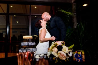 Ashley and Hill kissing behind their cake, Pensacola Waterfront Wedding, Ashley+Hill, Lazzat Photography