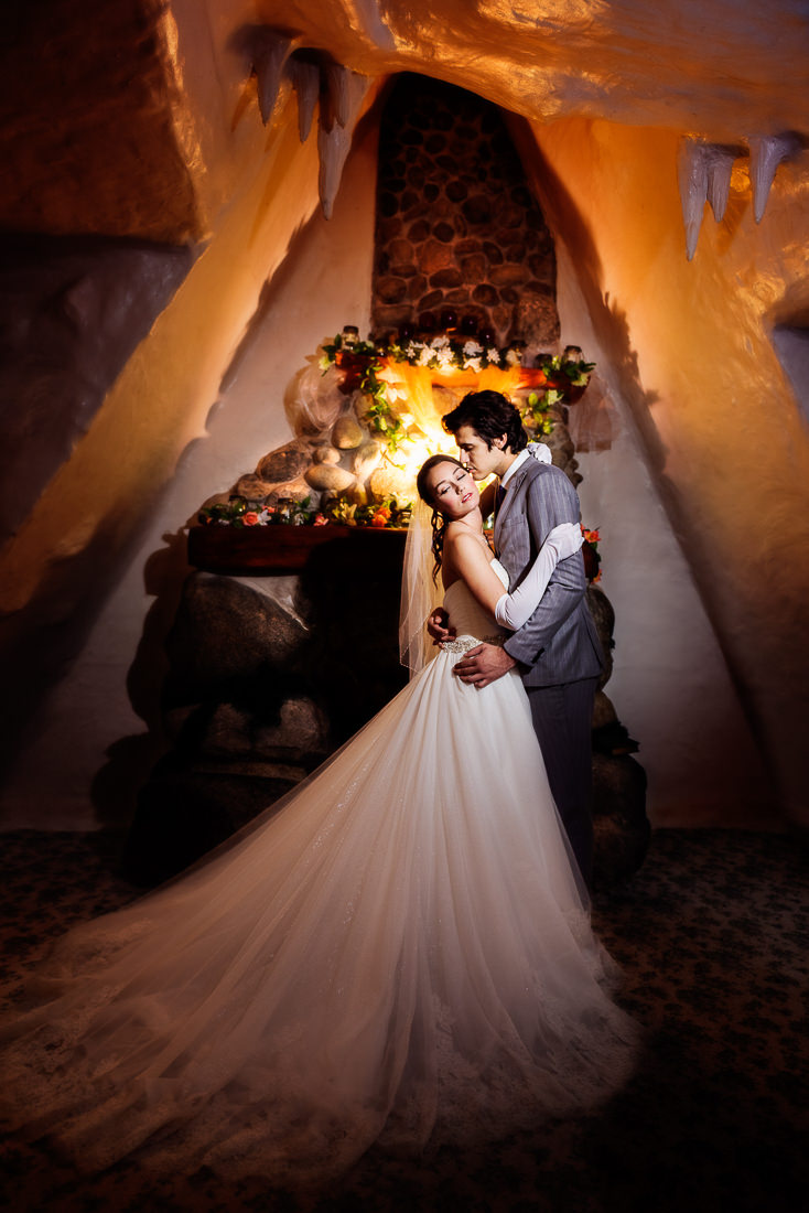 best wedding photographer Pensacola Orlando | creative imagery by Lazzat Photography | dramatic image indoors, cozy and intimate bride snuggling to groom while he is kissing her cheek.